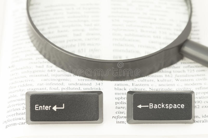 Enter and Backspace Computer Keys and a Lens on a Book Page stock image