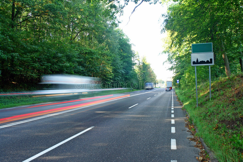 Entering a city by car. Blurred motion road, empty city limits signs, wide asphalt road. Copy space royalty free stock photography