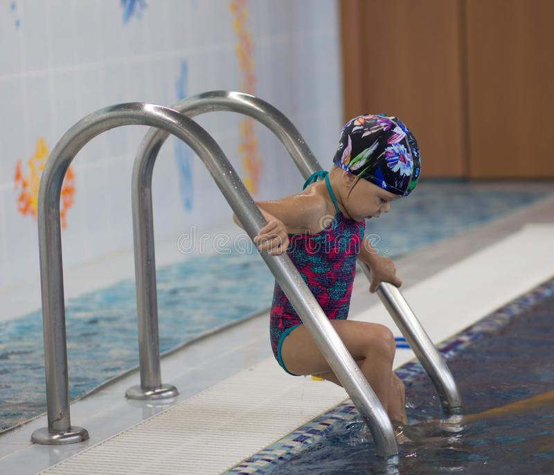 Child entering the swimming pool stock image