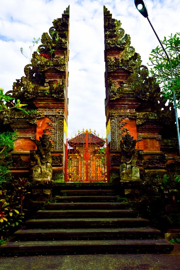 Stone red ancient gate to a sacred temple in Ubud, Bali for people to pray and worship. Entering gate to a sacred place for local traditional village people to stock image