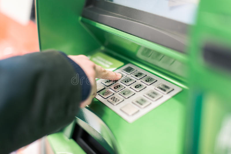 Entering PIN on the ATM. Entering PIN on the green ATM royalty free stock photography
