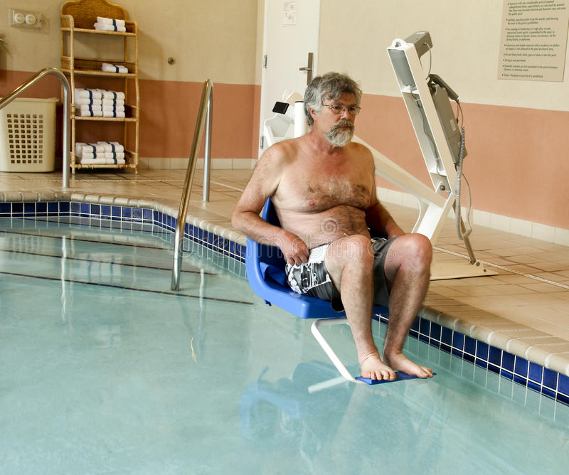 Entering pool with a handicapped lift. Man being put into a swimming pool by a handicapped lift stock images