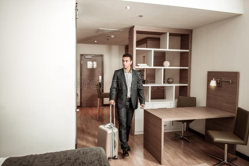 Young businessman entering hotel room with his luggage. Entering room. Young businessman wearing dark suit entering hotel room with his luggage stock photo