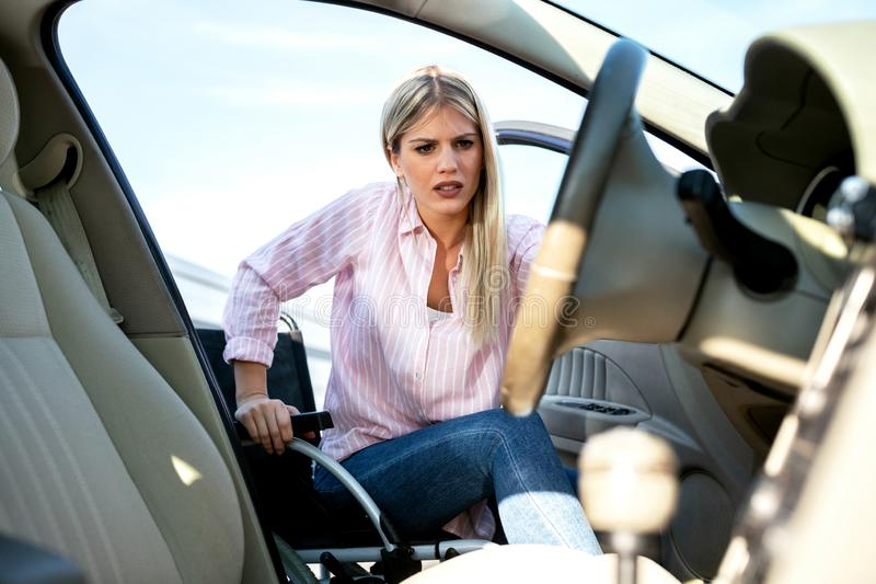 Entering your car can be a little tricky if you are physically challenged. Young blonde woman with loss of leg function stock photography
