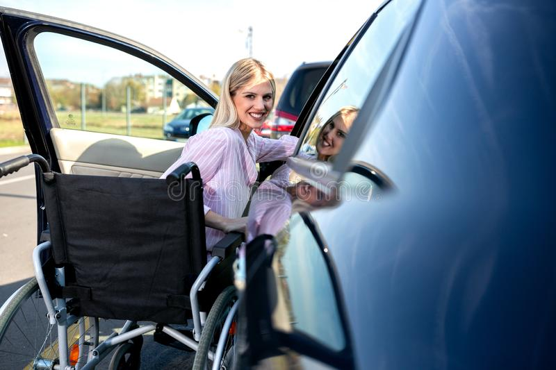 Entering your car can be a little tricky if you are physically challenged. Young blonde woman with loss of leg function stock images