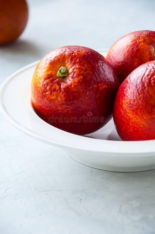 Entero maduro fresco y rebanadas de naranjas de sangre en una placa en un whi foto de archivo libre de regalías