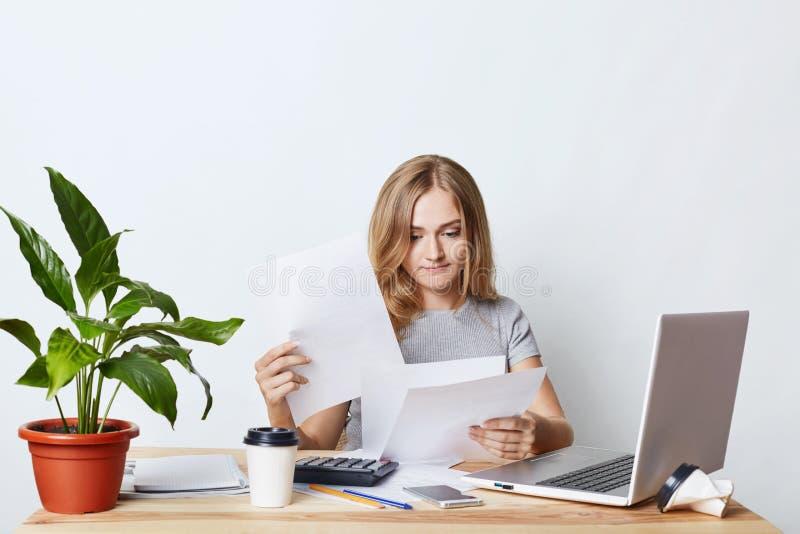 Enterpreneur femelle occupé regardant par des documents, se reposant la table dans son coffret, fonctionnant avec l'ordinateur po photos stock