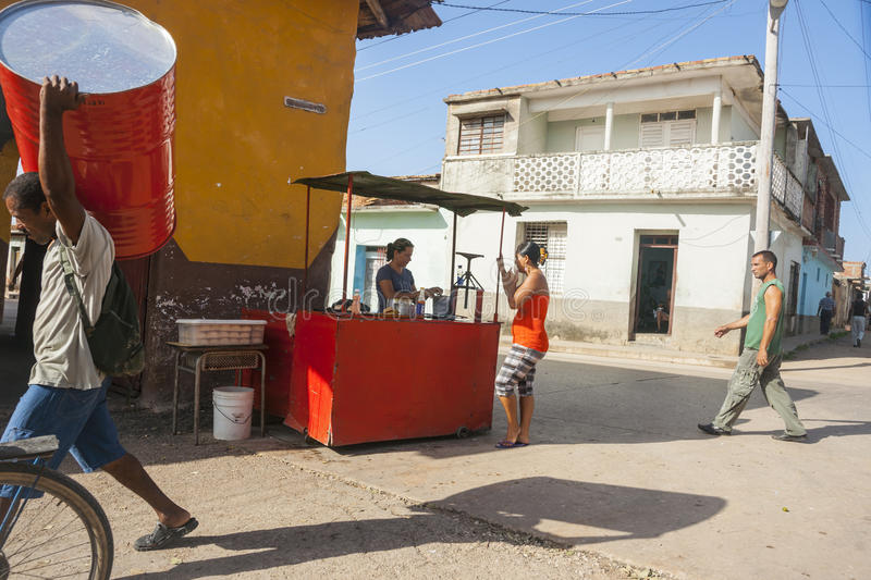 Enterprise on Cuban street corner. Trinidad, Cuba - July 2, 2012: Street corner takeaway food stall third world style with woman buying while a man carries a royalty free stock image