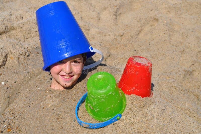 Enterré dans le sable images stock