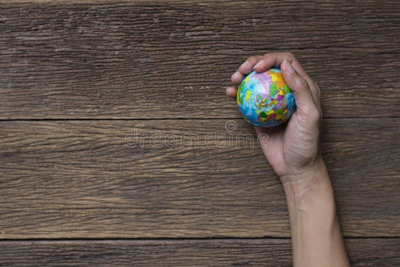 Enterre o planeta na mão fêmea na tabela de madeira foto de stock royalty free