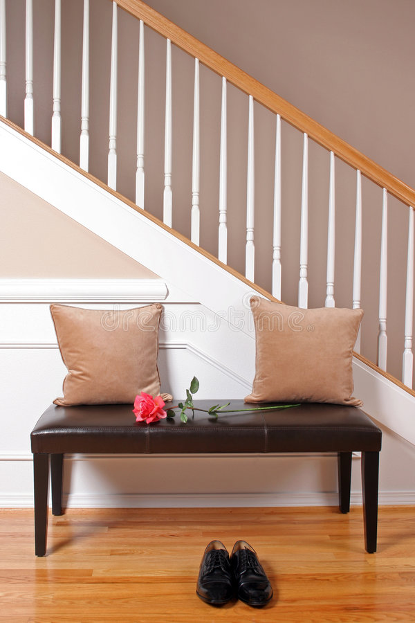 Entertaining a Guest. An entryway with dress shoes and a flower stock photos