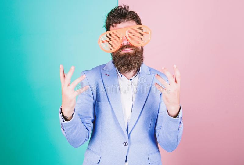Entertaining himself. Bearded man wearing party goggles. Funny hipster in extravagant glasses, fashion accessory. Fashion man with long beard in formal wear royalty free stock images