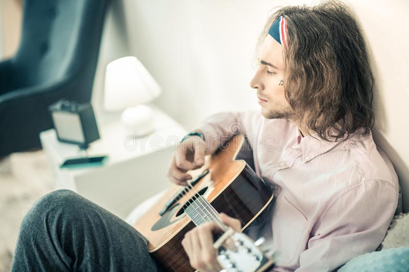 Emotional long-haired artist being concentrated on personal musical instrument. Entertaining himself. Emotional long-haired artist being concentrated on personal royalty free stock images