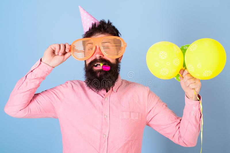 Entertainment artist leading contest at kids party, International children day celebration. Bearded man with birthday. Cap, huge glasses, party wistle and royalty free stock photos