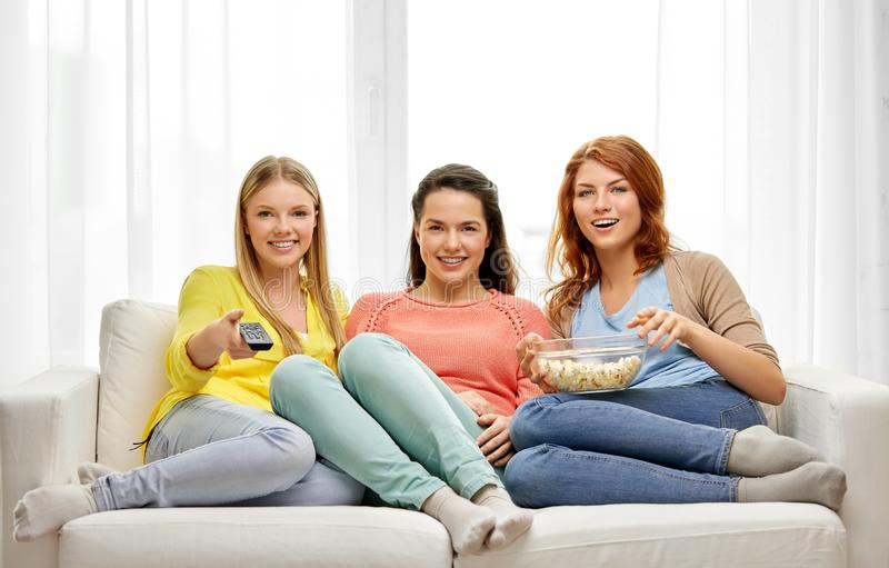 Teenage girls or friends watching tv at home royalty free stock images