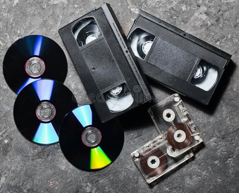 Entertainment and media technology from the 90s. CD& x27;s, audio cassettes, video cassettes on a black concrete surface. Top view royalty free stock photos