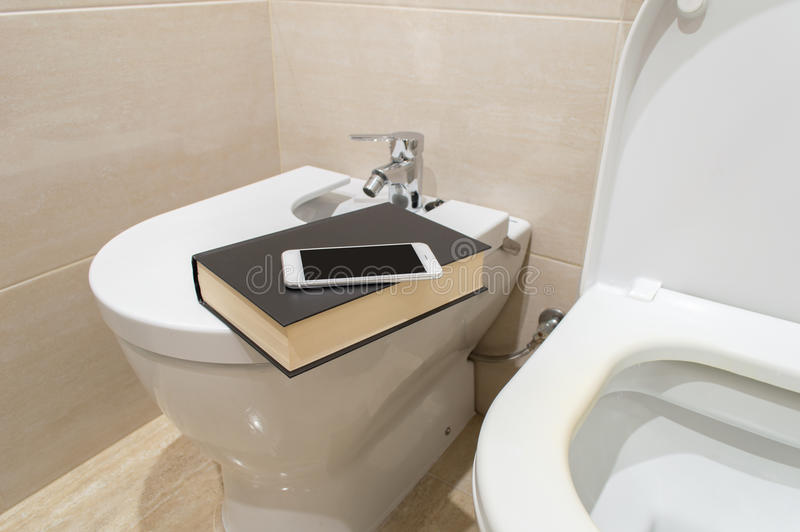 Entertainment in the wc. Entertainment in the toilet withe with a smartphone or a book royalty free stock image