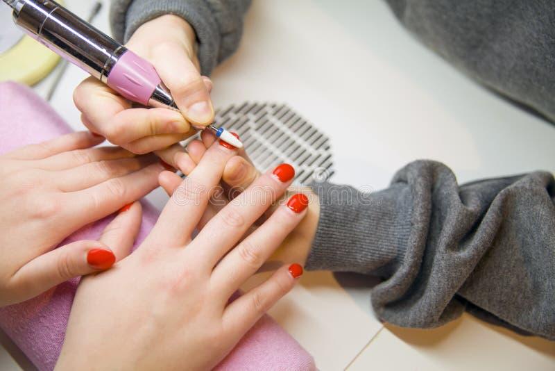 Entfernen Sie alten Nagellack, Maniküre Mahlen von Nägeln Entfernen der Nagelplatte mit einer Fräsmaschine stockfotos