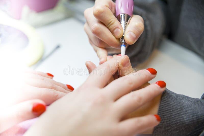 Entfernen Sie alten Nagellack, Maniküre Mahlen von Nägeln Entfernen der Nagelplatte mit einer Fräsmaschine stockfotografie