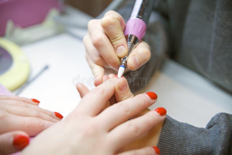 Entfernen Sie alten Nagellack, Maniküre Mahlen von Nägeln Entfernen der Nagelplatte mit einer Fräsmaschine lizenzfreie stockfotografie