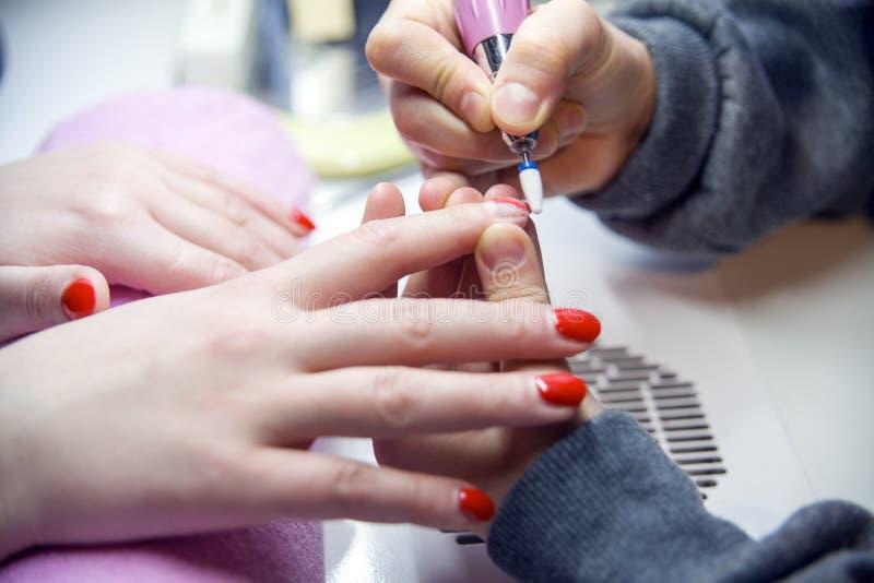 Entfernen Sie alten Nagellack, Maniküre Mahlen von Nägeln Entfernen der Nagelplatte mit einer Fräsmaschine stockbilder