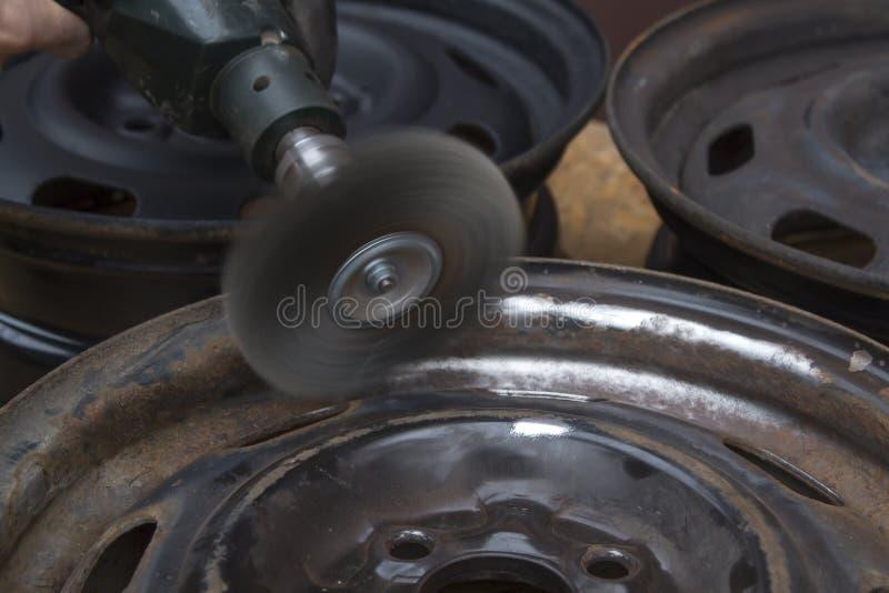 Entfernen Sie den Rost von der alten Autokante unter Verwendung einer Drahtbürste, die zum Bohrgerät befestigt wird stockfoto