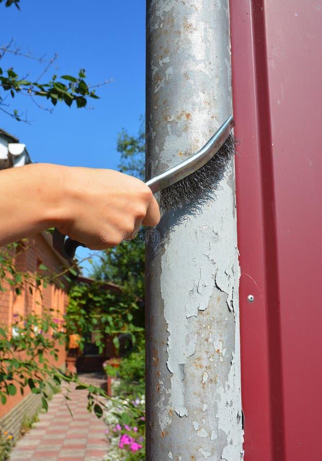 Entfernen Sie die alte Farbe von der Oberfläche Benutzen Sie eine Drahtbürste, um die Farbe vom Metall abzustreifen und Rost zu e stockbild