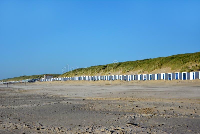 Entfernte Ansicht der langen Reihe der weißen und blauen Strandhallen auf dem Strand in Texel in den Niederlanden stockbilder