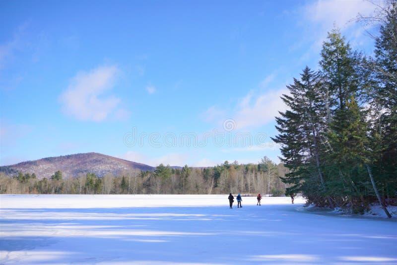 Entfernte snowshoers kreuzen gefrorenen See am sonnigen Wintertag lizenzfreies stockfoto