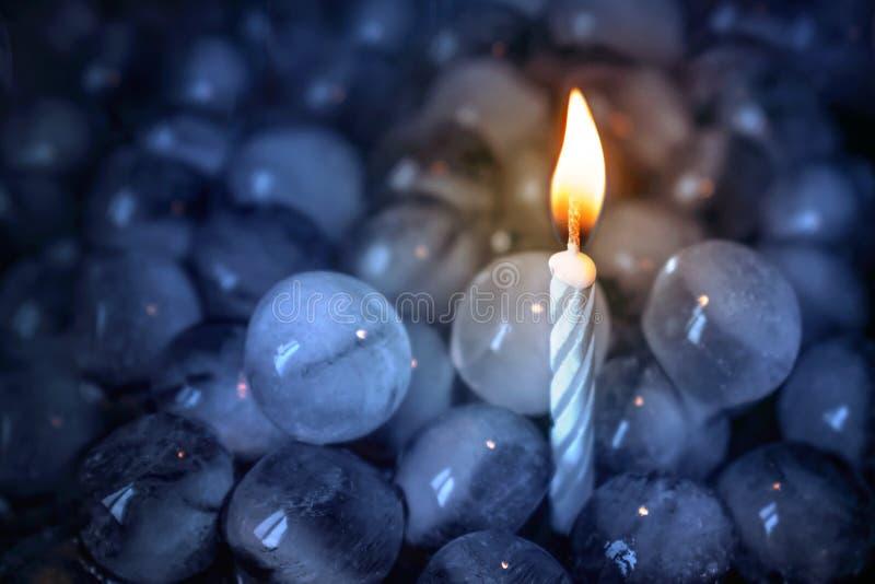 entgegengesetzte Eis und Feuer Eine brennende einsame Kerze unter Eisbällen lizenzfreies stockbild