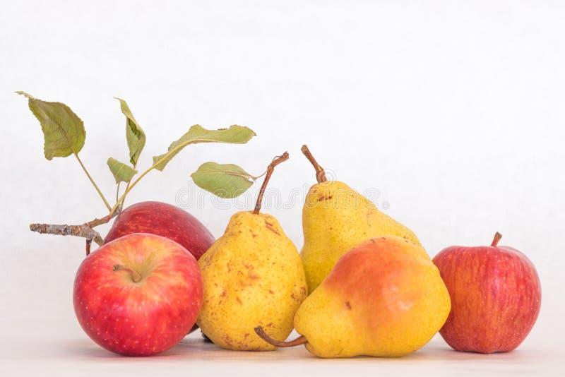 Enthäutete reifes Gelb drei Birnen und rote Äpfel, neue organische schöne Atelieraufnahme mit Stamm und Grünblätter lizenzfreies stockfoto