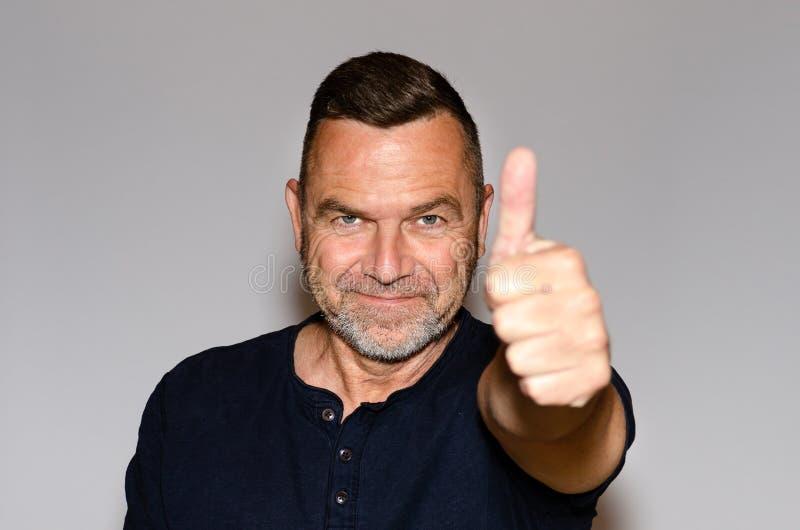 Enthousiaste gemotiveerde mens die een duim opgeven stock foto