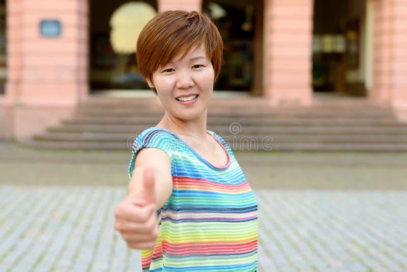 Enthousiaste gemotiveerde vrouw die een duim opgeven royalty-vrije stock afbeelding
