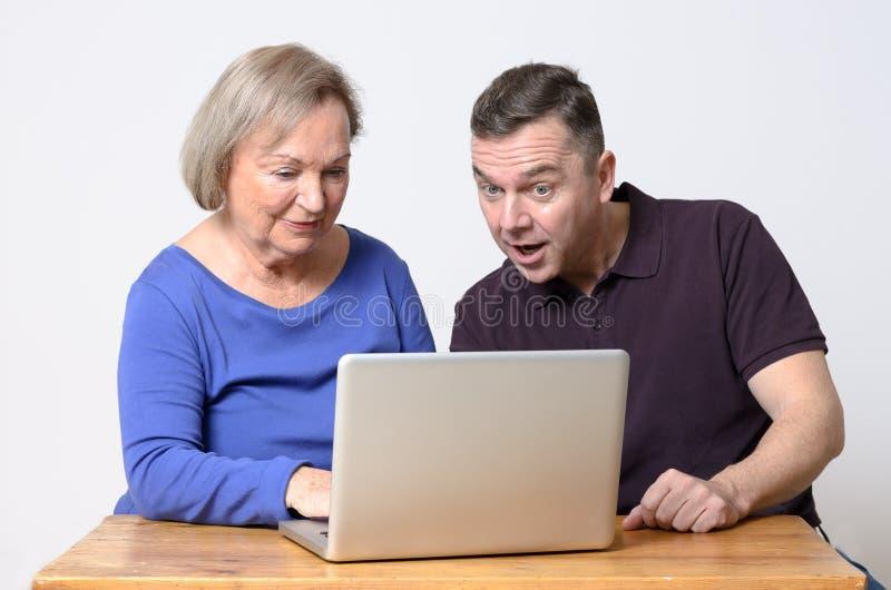 Enthousiaste man die laptop met vrouw bekijken royalty-vrije stock foto's