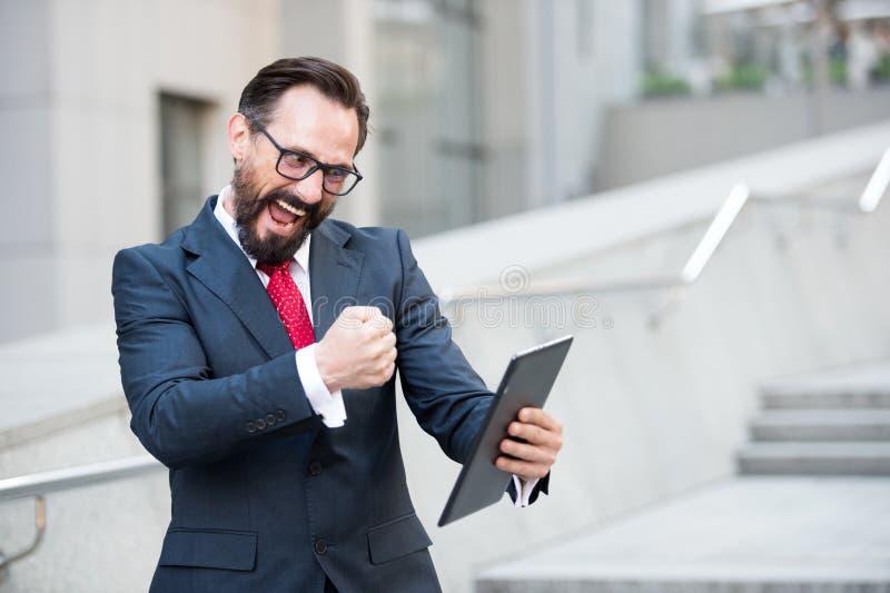 Enthousiaste ondernemer die opwinding uitdrukken terwijl het gebruiken van digitale tablet stock foto's