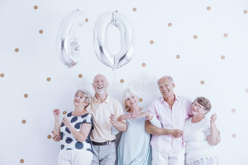 Enthousiaste oudsten met zilveren ballons royalty-vrije stock foto's