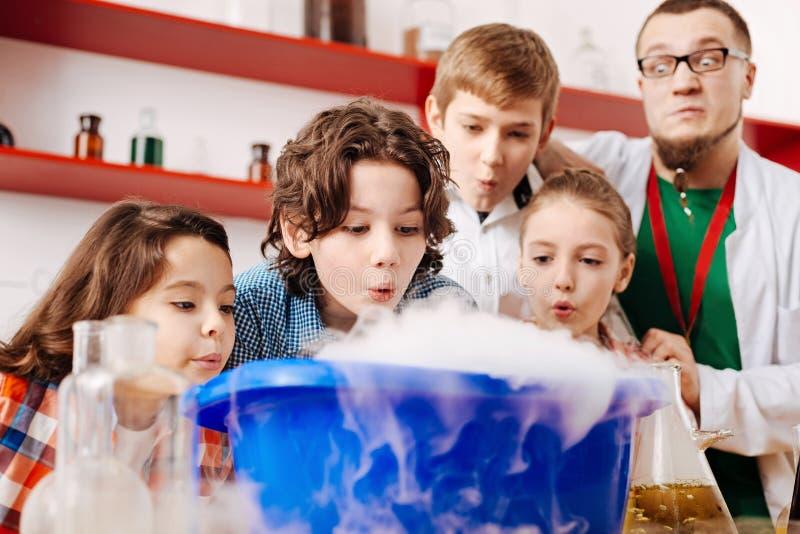 Enthousiaste positieve kinderen die op de chemische damp blazen stock afbeeldingen