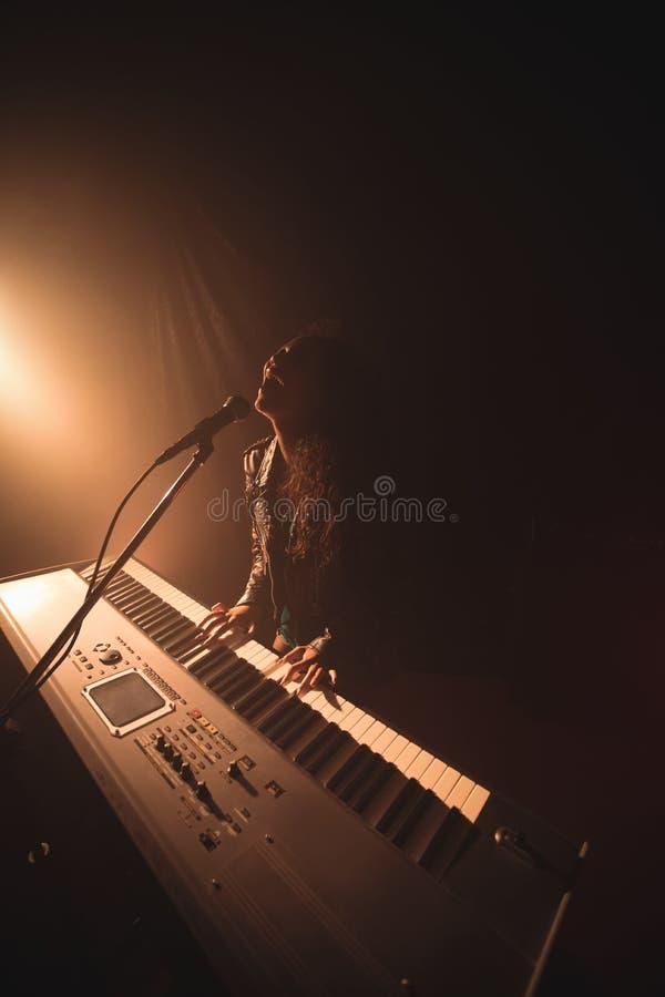 Enthousiaste vrouwelijke zanger het spelen piano bij muziekoverleg stock afbeelding