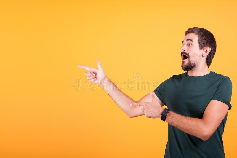 Enthusiasm and expressive man pointing at the copyspace. Available for your text, promo or advertising. The male is surprised and happy. Orange background royalty free stock photography