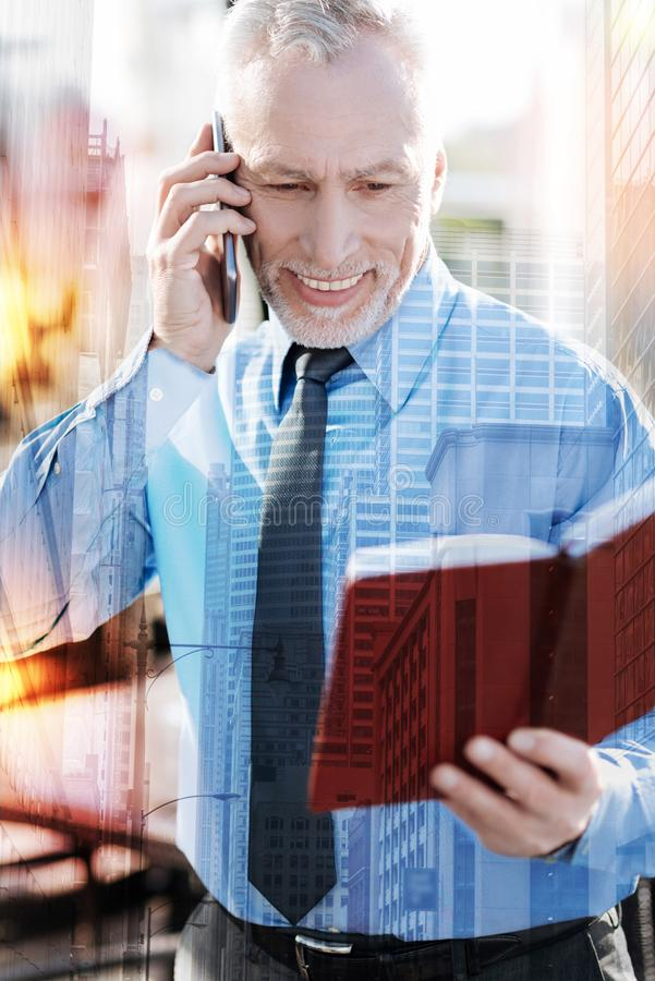 Enthusiastic businessman smiling and talking on the phone. Business talk. Cheerful experienced mature businessman looking at his schedule in a notebook and stock photos