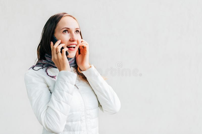 Enthusiastic Caucasian young woman in white jacket talks by mobile phone. Good news royalty free stock photo