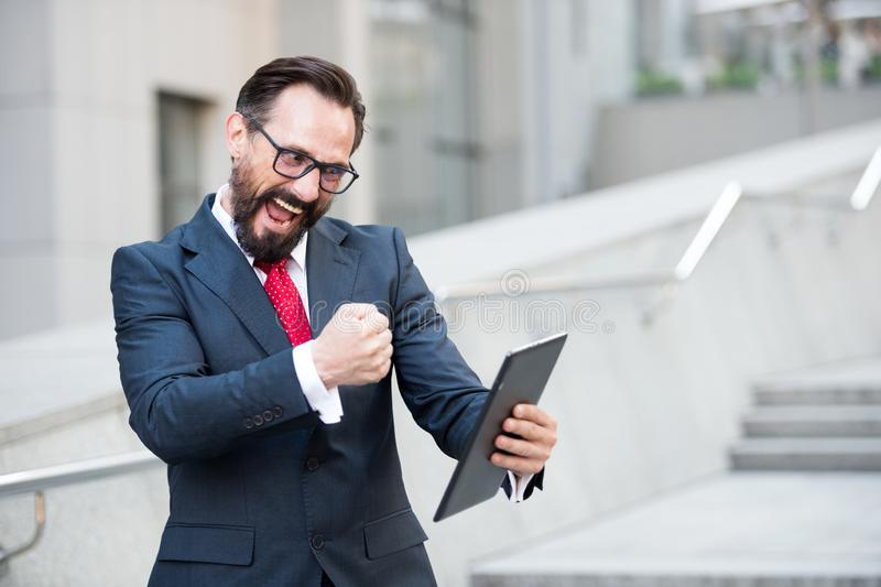 Enthusiastic entrepreneur expressing excitement while using digital tablet. Waist up of bearded active entrepreneur using digital tablet and showing his fist to stock photos