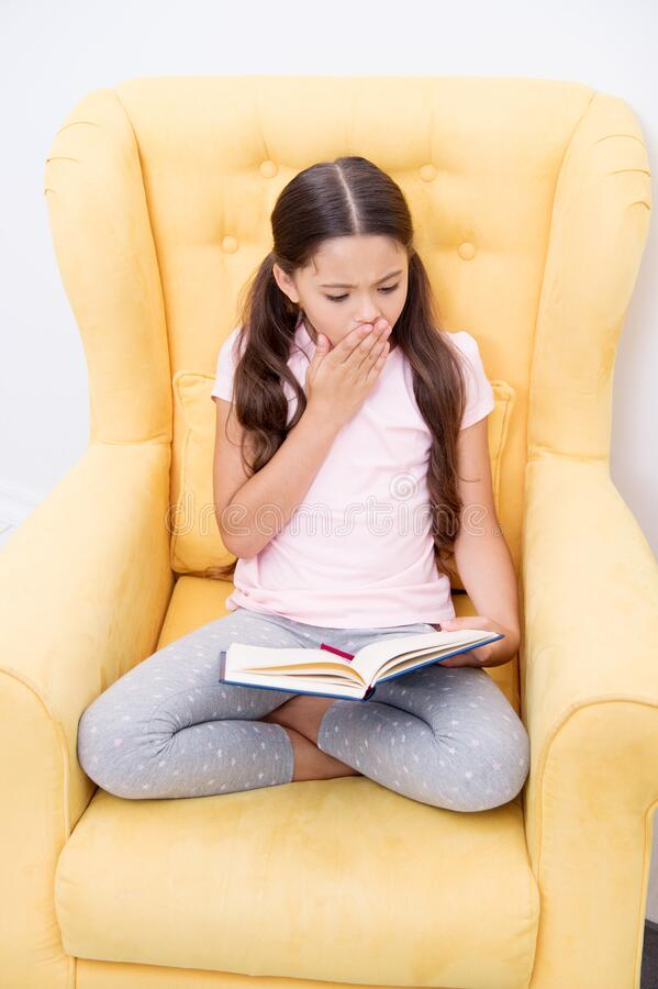 Enthusiastic about exciting story. Reading hobby. Girl child sit yellow armchair read book. Kid cute bookworm. Girl kid royalty free stock images
