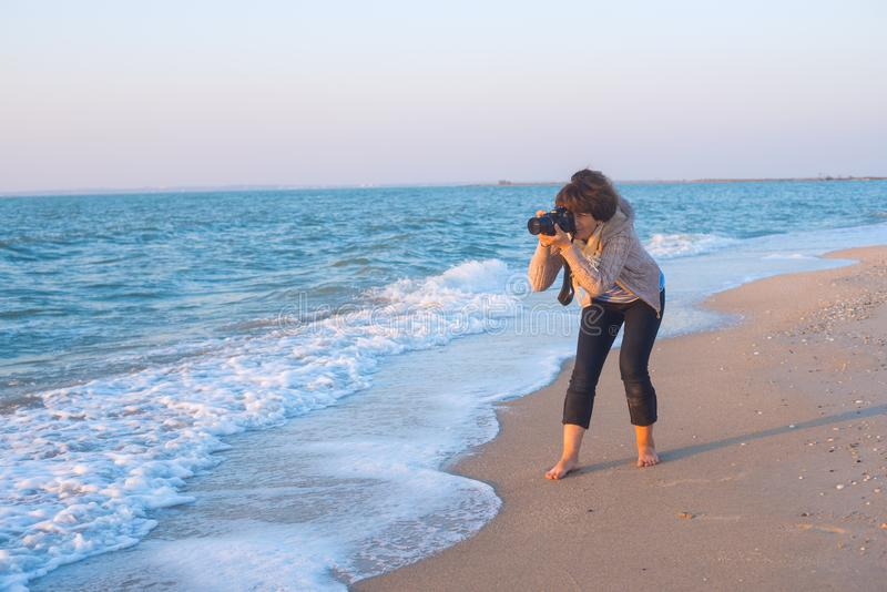 An enthusiastic female photographer takes a picture stock photo