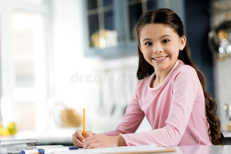 Enthusiastic gay girl working on home assignment royalty free stock image