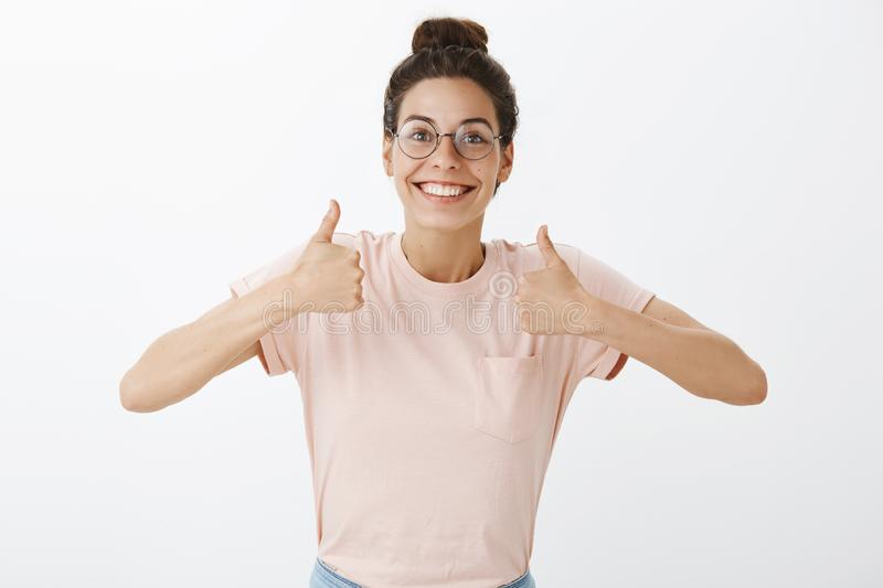 Enthusiastic happy and good-looking nice girl in glasses and t-shirt raising thumbs up in support and cheer smiling stock images