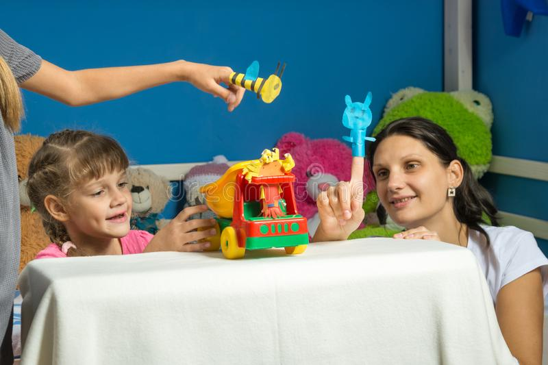 An enthusiastic mother plays with daughters in a self-made finger puppet theater royalty free stock photo