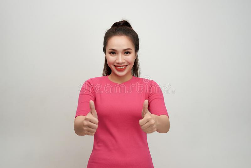Enthusiastic motivated attractive young woman giving a thumbs up gesture of approval and success with a beaming smile royalty free stock photo