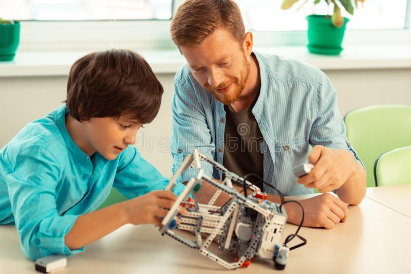 Teacher explaining to pupil robots mode of operation. Enthusiastic people. Smiling teacher with remote control explaining to a pupil mode of operation f a robot royalty free stock image