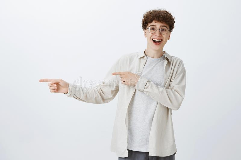 Enthusiastic and playful handsome hipster boy with curly hair in round eyewear smiling energized and happy as pointing stock image